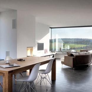 Modern inredning av ett mellanstort allrum med öppen planlösning, med betonggolv, vita väggar, en väggmonterad TV, en öppen hörnspis och en spiselkrans i gips