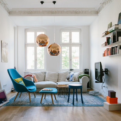 Inspiration for a mid-sized eclectic enclosed light wood floor family room remodel in Berlin with white walls, a wall-mounted tv and no fireplace