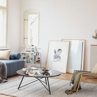 Mittelgroßes Skandinavisches Wohnzimmer mit weißer Wandfarbe, braunem Holzboden und braunem Boden in Berlin