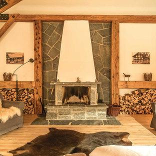 Mittelgroßes, Fernseherloses, Abgetrenntes Uriges Wohnzimmer mit beiger Wandfarbe, hellem Holzboden, Kaminofen, Kaminumrandung aus Stein und braunem Boden in München