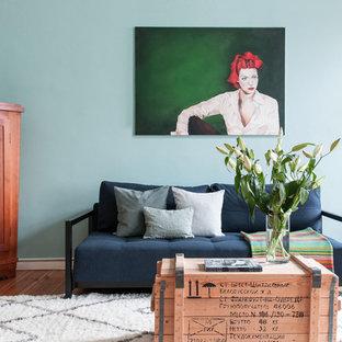 Kleines, Fernseherloses Stilmix Wohnzimmer ohne Kamin mit blauer Wandfarbe, hellem Holzboden und braunem Boden in Berlin