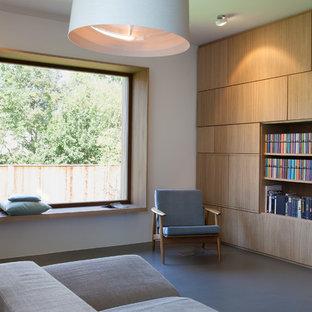Aménagement d'un salon avec une bibliothèque ou un coin lecture de taille moyenne et fermé avec un mur blanc et un sol en linoléum.