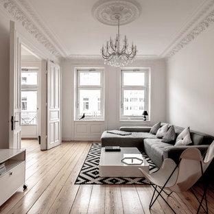 Nordisches Wohnzimmer mit weißer Wandfarbe, braunem Holzboden und braunem Boden in Hamburg