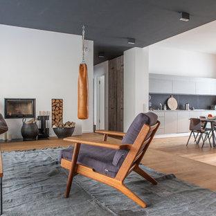 Offenes, Mittelgroßes Skandinavisches Wohnzimmer mit weißer Wandfarbe, braunem Holzboden, Kamin und verputztem Kaminsims in Berlin