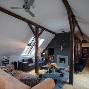 Kleines, Repräsentatives, Fernseherloses, Offenes Uriges Wohnzimmer mit schwarzer Wandfarbe, hellem Holzboden, Kamin, beigem Boden und Kaminsims aus Beton in Hamburg