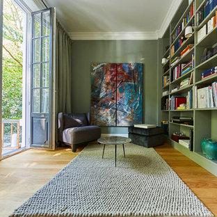 Idées déco pour une salle de séjour avec une bibliothèque ou un coin lecture contemporaine de taille moyenne et fermée avec un mur vert, un sol en bois clair, aucune cheminée, aucun téléviseur et un sol marron.