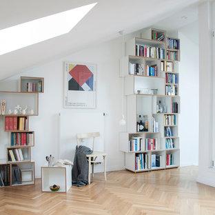 Mittelgroße, Fernseherlose, Abgetrennte Nordische Bibliothek ohne Kamin mit weißer Wandfarbe, braunem Holzboden und braunem Boden in Berlin