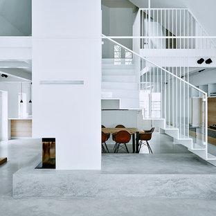 Großes, Offenes Modernes Wohnzimmer Mit Weißer Wandfarbe, Betonboden,  Verputztem Kaminsims Und Eckkamin In