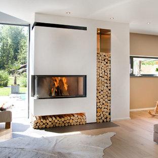 Foto de sala de estar abierta, contemporánea, con paredes beige, chimenea de esquina, marco de chimenea de yeso y suelo de madera clara