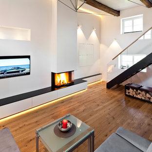 Idee per un ampio soggiorno design aperto con sala formale, pareti bianche, pavimento in legno verniciato, cornice del camino in intonaco, parete attrezzata, pavimento marrone e camino sospeso