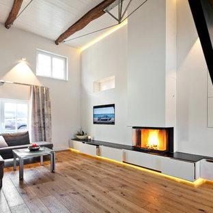 他の地域の巨大なコンテンポラリースタイルのおしゃれなLDK (フォーマル、白い壁、塗装フローリング、漆喰の暖炉まわり、埋込式メディアウォール、茶色い床、吊り下げ式暖炉) の写真