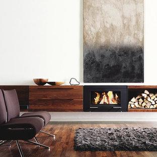 Esempio di un soggiorno moderno di medie dimensioni e aperto con camino sospeso, pareti bianche, parquet scuro e cornice del camino in metallo
