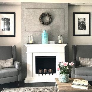 Modelo de sala de estar cerrada, clásica, pequeña, con paredes grises, suelo de baldosas de porcelana, estufa de leña, marco de chimenea de yeso, televisor retractable y suelo negro