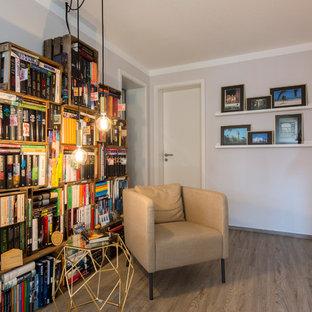 Kleine, Fernseherlose Moderne Bibliothek ohne Kamin mit grauer Wandfarbe und braunem Holzboden in Nürnberg