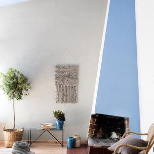 Fernseherloses Nordisches Wohnzimmer mit blauer Wandfarbe, Eckkamin und hellem Holzboden in Dresden