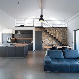 Großes, Repräsentatives, Fernseherloses Industrial Wohnzimmer im Loft-Stil, ohne Kamin mit Betonboden, grauem Boden und weißer Wandfarbe in Sonstige