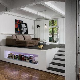 Ejemplo de salón tipo loft, industrial, pequeño, sin chimenea y televisor, con paredes blancas y suelo de madera en tonos medios
