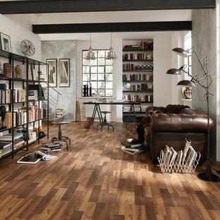 他の地域の広いインダストリアルスタイルのおしゃれなリビングロフト (ライブラリー、白い壁、ラミネートの床、茶色い床) の写真