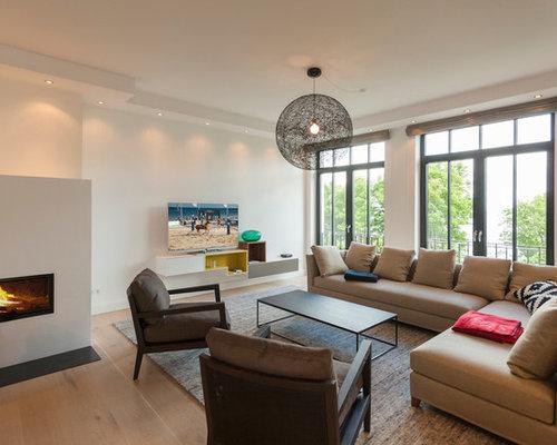 gerumiges offenes modernes wohnzimmer mit weier wandfarbe braunem holzboden kamin verputztem kaminsims - Wohnzimmer Mit Kamin Bilder
