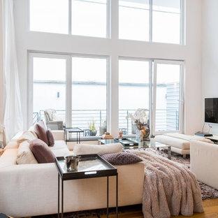 Modernes Wohnzimmer mit weißer Wandfarbe, braunem Holzboden, freistehendem TV und braunem Boden in Köln