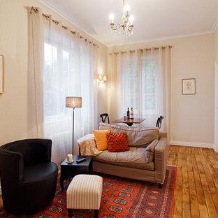 Idée de décoration pour un salon tradition de taille moyenne et ouvert avec un mur beige, un sol en bois brun et aucun téléviseur.