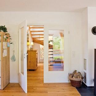Offenes Landhausstil Wohnzimmer mit weißer Wandfarbe, gebeiztem Holzboden, Kaminofen, Kaminumrandung aus Metall und braunem Boden in Sonstige