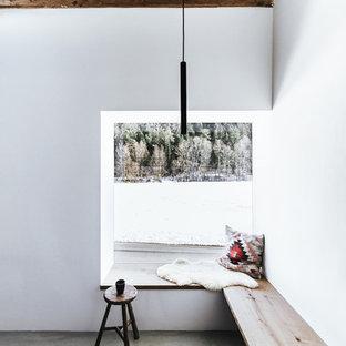 Uriges Wohnzimmer mit weißer Wandfarbe, Betonboden und grauem Boden in München