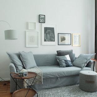 Modelo de sala de estar tipo loft, nórdica, pequeña, sin chimenea y televisor, con paredes blancas, suelo laminado y suelo marrón