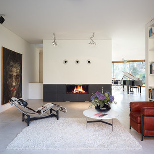 Inspiration for a large modern open concept gray floor family room remodel in Berlin with white walls, a standard fireplace and a metal fireplace