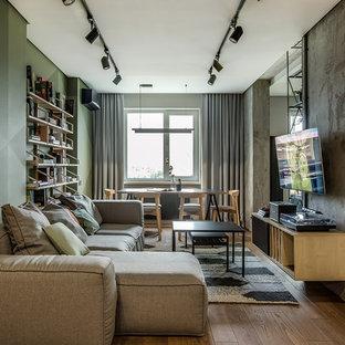Cette image montre une salle de séjour design de taille moyenne et ouverte avec un mur vert, un sol en bois brun, un téléviseur fixé au mur et un sol marron.