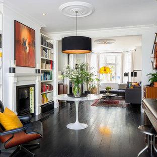 Offenes, Großes, Fernseherloses Modernes Musikzimmer mit weißer Wandfarbe, dunklem Holzboden, Kaminumrandung aus Stein, Kamin und schwarzem Boden in Hamburg