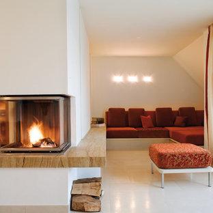 ミュンヘンの中サイズのコンテンポラリースタイルのおしゃれなファミリールーム (ベージュの壁、両方向型暖炉、石材の暖炉まわり) の写真