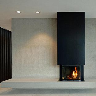 Esempio di un grande soggiorno moderno stile loft con pareti grigie, pavimento in pietra calcarea, camino sospeso, cornice del camino in metallo e pavimento grigio