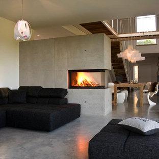 他の地域の大きいモダンスタイルのおしゃれなLDK (白い壁、コンクリートの床、コンクリートの暖炉まわり、コーナー設置型暖炉、グレーの床) の写真