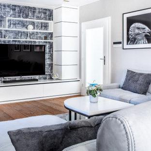 Mittelgroßes Modernes Wohnzimmer mit grauer Wandfarbe, braunem Holzboden, Wand-TV, braunem Boden und Tapetenwänden in Berlin