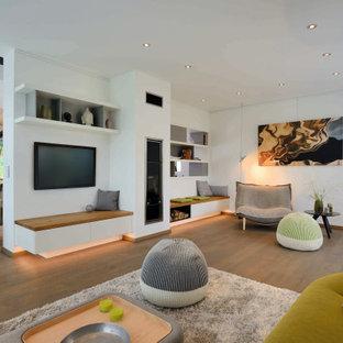 Offenes Modernes Wohnzimmer mit weißer Wandfarbe, braunem Holzboden, Wand-TV und braunem Boden in Sonstige