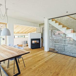 他の地域の大きいコンテンポラリースタイルのおしゃれなリビングロフト (フォーマル、白い壁、淡色無垢フローリング、薪ストーブ、金属の暖炉まわり、内蔵型テレビ、茶色い床) の写真