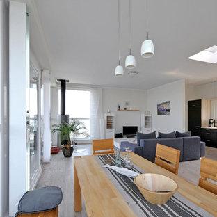 ベルリンの広いビーチスタイルのおしゃれなLDK (白い壁、淡色無垢フローリング、コーナー設置型暖炉、金属の暖炉まわり、埋込式メディアウォール、グレーの床) の写真