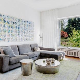 Fernseherloses Modernes Wohnzimmer ohne Kamin mit weißer Wandfarbe, hellem Holzboden und braunem Boden in Düsseldorf