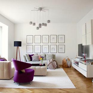 Modernes Wohnzimmer mit weißer Wandfarbe, braunem Holzboden, freistehendem TV und braunem Boden in Frankfurt am Main