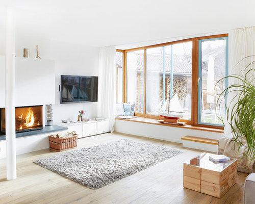 Mittelgroßes, Offenes Modernes Wohnzimmer Mit Weißer Wandfarbe, Braunem  Holzboden, Kaminsims Aus Beton,