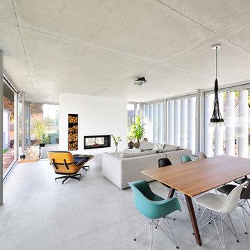 Offener Wohnbereich mit Betonboden und Tunnelkamin