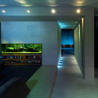 フランクフルトの中サイズのコンテンポラリースタイルのおしゃれなリビングロフト (グレーの壁、コンクリートの床、暖炉なし) の写真