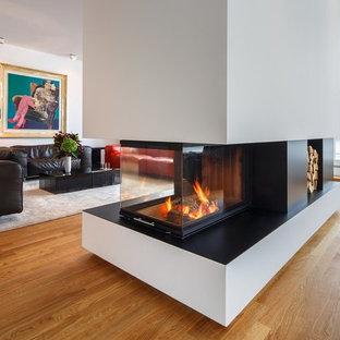 ベルリンの大きいコンテンポラリースタイルのおしゃれなファミリールーム (ライブラリー、白い壁、無垢フローリング、薪ストーブ、コンクリートの暖炉まわり、テレビなし、ベージュの床) の写真