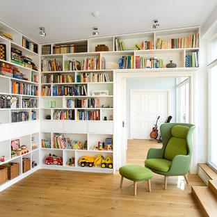 Esempio di un soggiorno design di medie dimensioni e chiuso con libreria, pareti bianche, pavimento in legno massello medio, nessun camino e nessuna TV