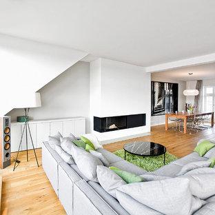Großes, Fernseherloses, Offenes Modernes Wohnzimmer Mit Weißer Wandfarbe,  Braunem Holzboden, Kamin Und