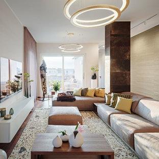 Offenes, Großes Modernes Wohnzimmer mit dunklem Holzboden, Tunnelkamin, Kaminumrandung aus Stein, Wand-TV, beiger Wandfarbe und braunem Boden in Berlin