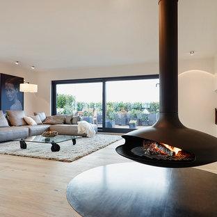 Imagen de salón abierto, contemporáneo, grande, sin televisor, con paredes blancas, suelo de madera clara y chimeneas suspendidas