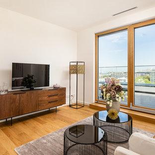 Repräsentatives, Abgetrenntes, Kleines Modernes Wohnzimmer ohne Kamin mit weißer Wandfarbe, braunem Holzboden, freistehendem TV und beigem Boden in München