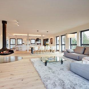 Imagen de salón abierto, contemporáneo, extra grande, con paredes blancas, suelo de madera clara y chimeneas suspendidas